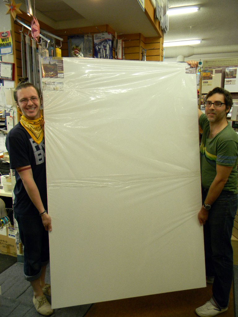 """Wet Paint staffers, Chris and Justin, holding a giant 48x72"""" stretched canvas"""